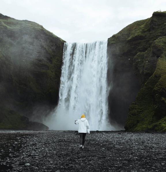 person walking towards a waterfall