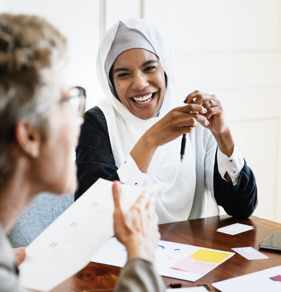 Women at a meeting smiling