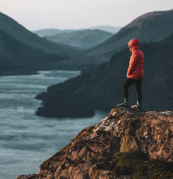 person standing at the edge of a cliff overlooking water